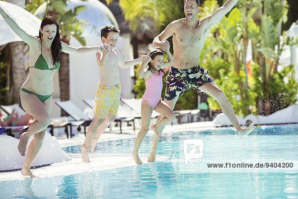 Eltern mit Sohn und Tochter beim Händchenhalten  Sprung ins Schwimmbad