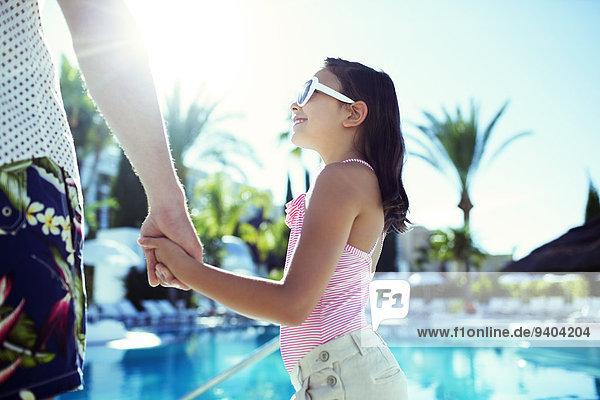 Mann hält sich mit seiner Tochter am Swimmingpool an den Händen