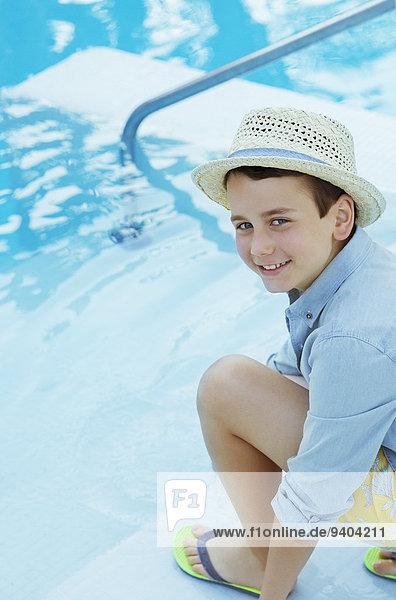 Porträt eines lächelnden Jungen mit Strohhut, der am Swimmingpool hockt