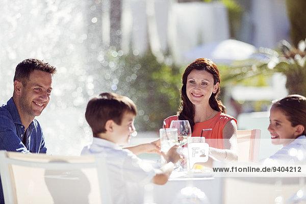 Familie mit zwei Kindern  die bei Tisch im Freien anstoßen