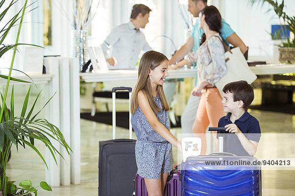 Familie mit Tochter und Sohn stehend mit Koffern in der Hotellobby