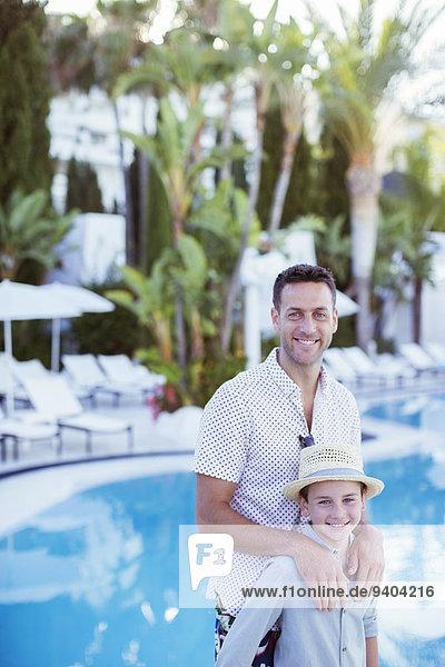 Porträt des lächelnden Vaters und Sohnes am Schwimmbad des Resorts
