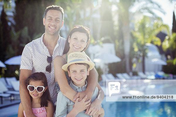 Porträt einer glücklichen Familie am Schwimmbad