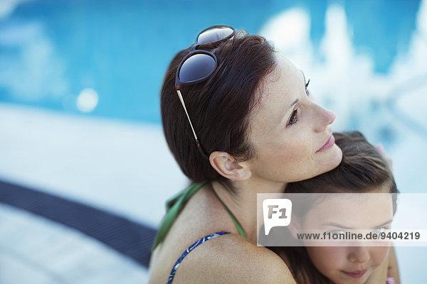Nachdenkliche Frau sitzend am Pool mit Tochter