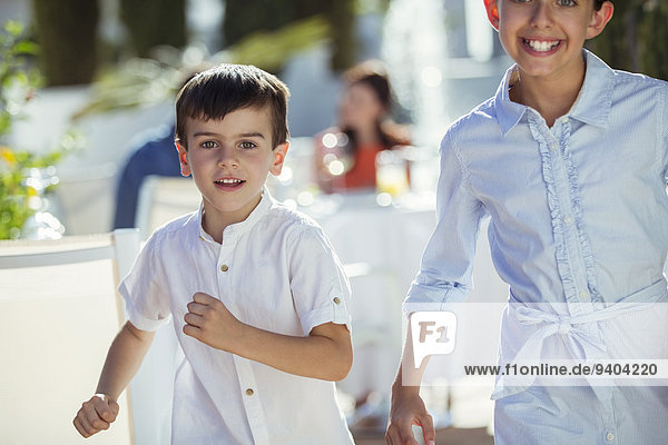 Lächelnder Junge und Mädchen rennen auf die Kamera zu.