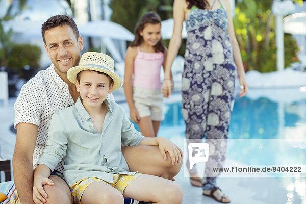 Familie  die sich am Schwimmbad vergnügt