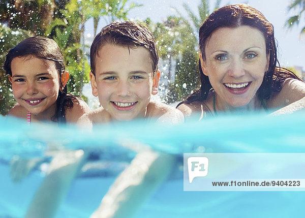 Portrait der Mutter mit ihren beiden Kindern im Schwimmbad