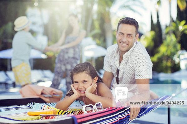 Porträt eines lächelnden Vaters und einer lächelnden Tochter am Schwimmbad, Mutter und Tochter im Hintergrund