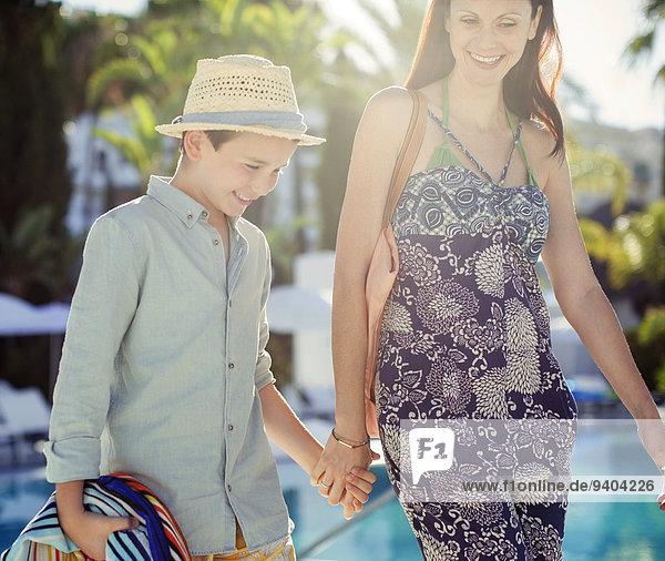 Mutter und Sohn halten Händchen am Schwimmbad