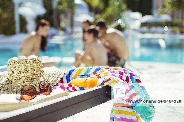 Sonnenhut  Sonnenbrille und buntes Strandtuch am Pool  Familie entspannt im Hintergrund