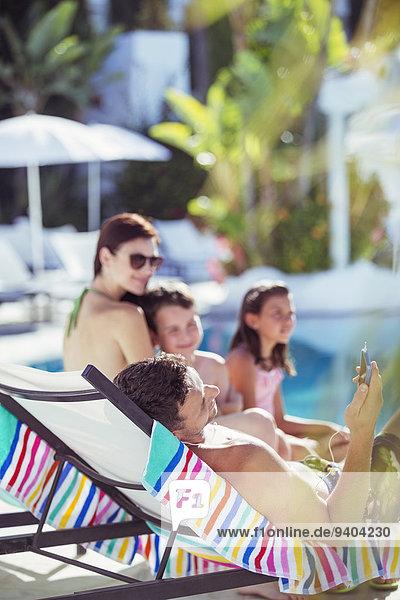 Familie mit zwei Kindern  die sich am Schwimmbad entspannen.