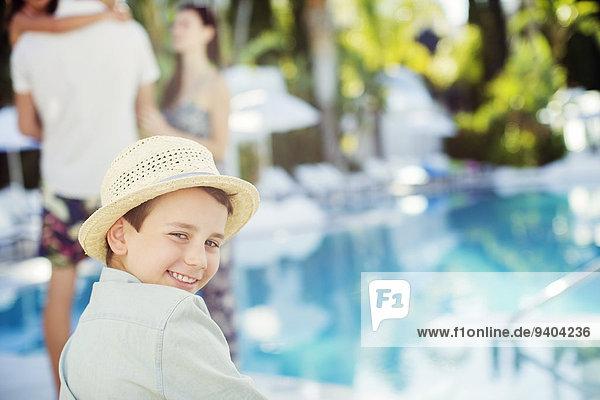 Porträt eines lächelnden Jungen mit Sonnenhut am Swimmingpool