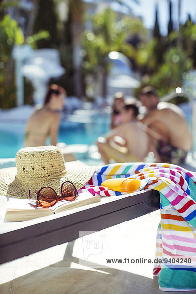 Sonnenhut  Sonnenbrille  Buch und buntes Strandtuch am Pool  Familie entspannt im Hintergrund