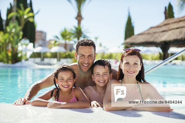 Porträt einer Familie mit zwei Kindern im Schwimmbad