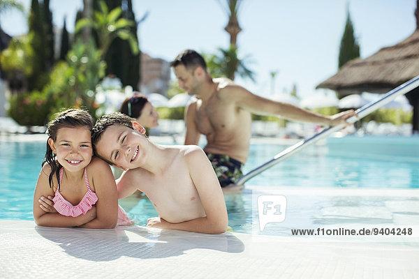 Porträt eines lächelnden Jungen und Mädchens im Schwimmbad