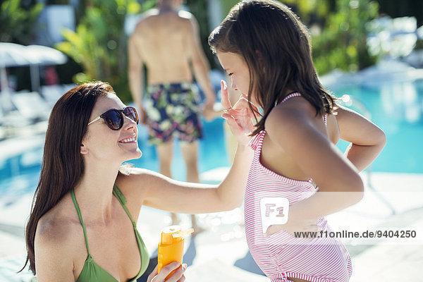 Mutter wendet Sonnencreme auf das Gesicht der Tochter am Schwimmbad an.