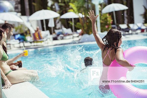 Mädchen mit rosa aufblasbarem Ring beim Sprung ins Schwimmbad, Familie im Hintergrund