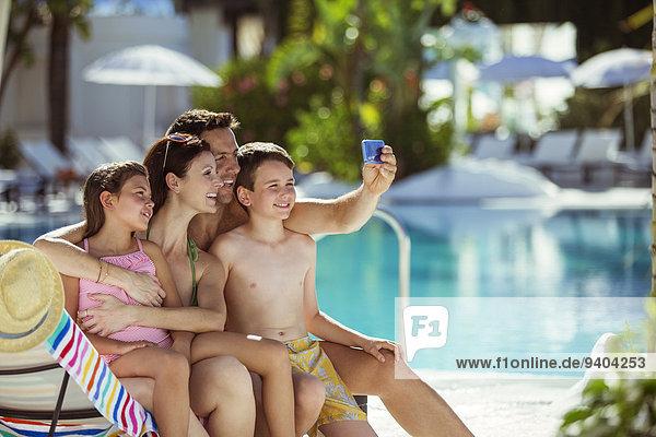 Familie mit zwei Kindern, die Selfie im Schwimmbad nehmen