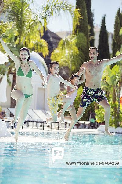Familie mit Sohn und Tochter, die Händchen halten und ins Schwimmbad springen.