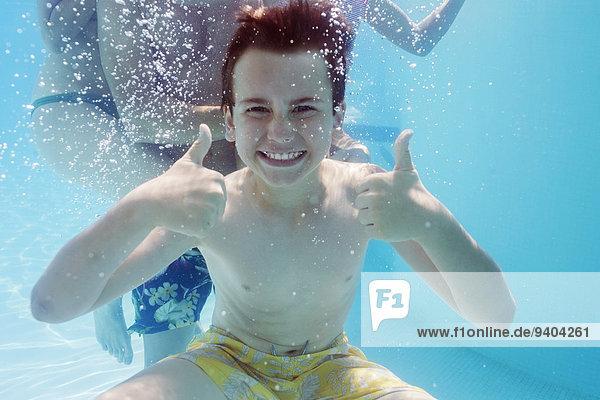 Portrait des Jungen mit Daumen nach oben unter Wasser, Person im Hintergrund