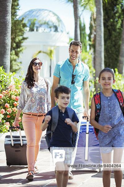 Familie mit Gepäck zu Fuß zum Ferienort