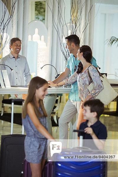 Familie mit Koffern im Gespräch mit der Rezeption in der Hotellobby