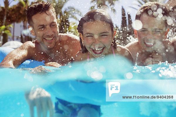 Vater schwimmt mit seinen beiden Kindern im Schwimmbad