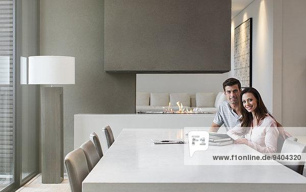 Porträt eines glücklichen Paares im Esszimmer mit Büchern und digitalem Tablett auf dem Tisch