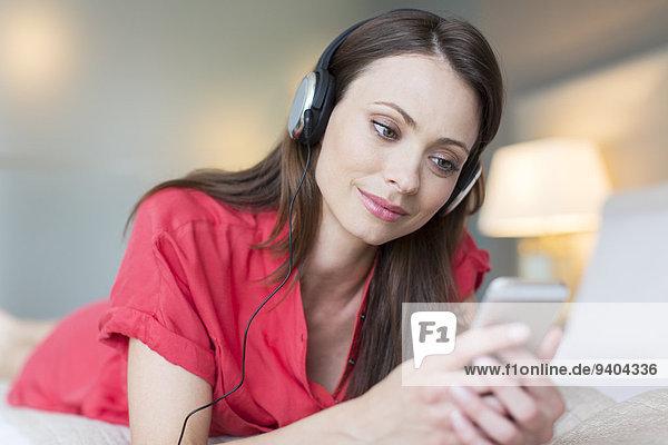 Lächelnde Frau im roten Kleid liegt auf dem Bett und hört Musik vom Smartphone.