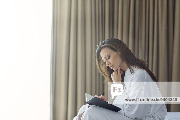 Nachdenkliche Frau im weißen Bademantel im Notizblock im Schlafzimmer