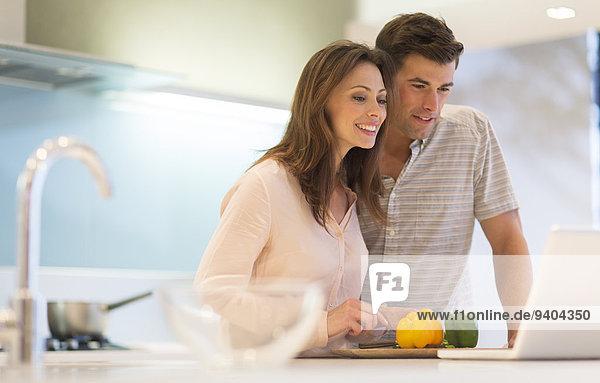 Lächelndes Paar schneidet Paprika und schaut auf den Laptop in der modernen Küche.