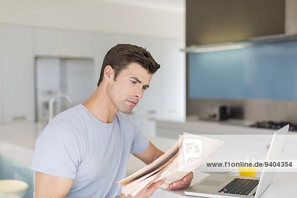 Mann liest Zeitung in der modernen Küche  Laptop und Orangensaft auf der Theke