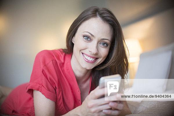 Porträt einer lächelnden Frau in rotem Kleid auf dem Bett liegend mit Smartphone