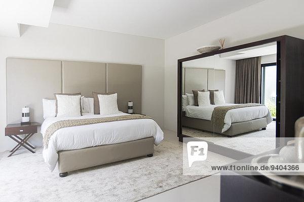 Modernes Schlafzimmer in Weiß und Beige mit Doppelbett-Spiegel