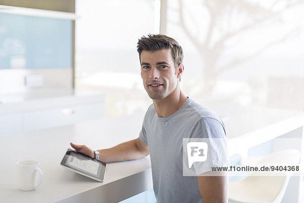 Porträt eines Mannes mit Tablet PC in der Küche