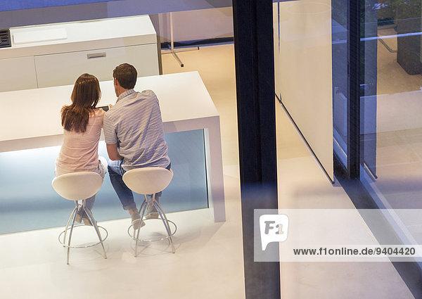 Rückansicht des Paares mit Tablet PC im Esszimmer