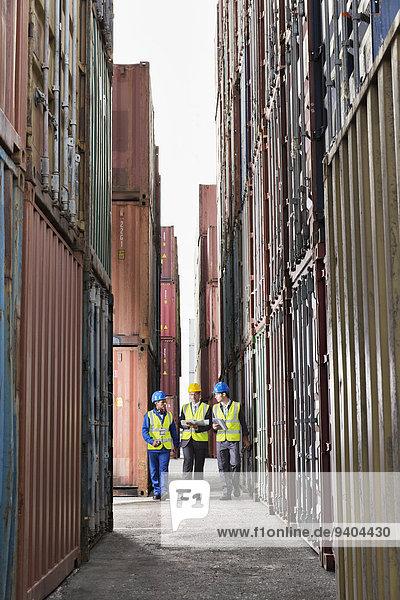 Arbeiter im Gespräch zwischen Frachtcontainern