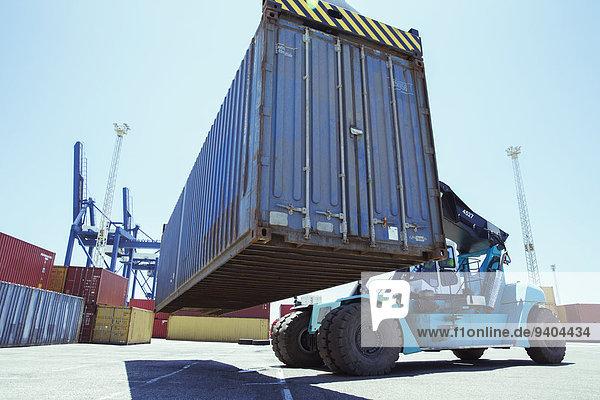 Niederwinkelansicht des Krans beim Heben von Frachtcontainern
