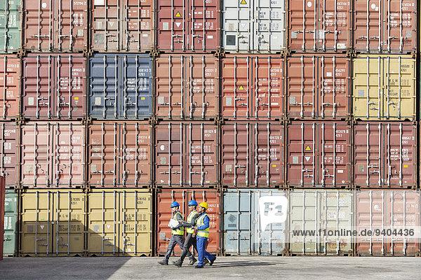 Arbeiter  die zusammen in der Nähe von Frachtcontainern gehen.