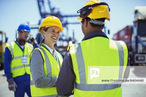 Geschäftsleute in Arbeitsschutzbekleidung sprechend