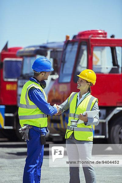 Geschäftsfrau und Arbeiter beim Händeschütteln in der Nähe von Lastwagen