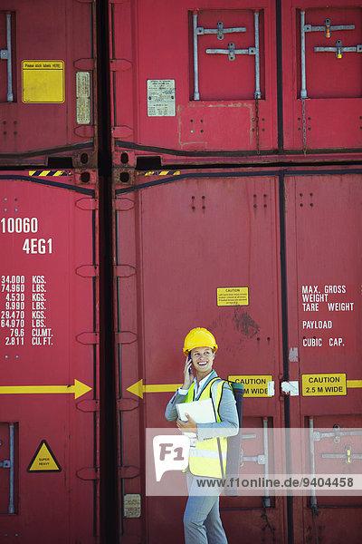 Geschäftsfrau im Gespräch am Handy in der Nähe von Frachtcontainern