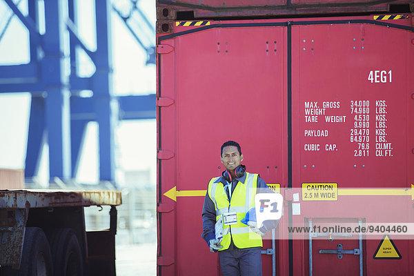 Arbeiter lächelt in der Nähe des Frachtcontainers