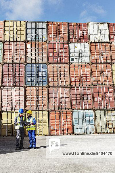 Geschäftsmann und Arbeiter im Gespräch in der Nähe von Frachtcontainern