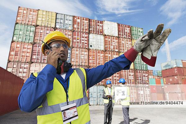Arbeiter mit Walkie-Talkie in der Nähe von Frachtcontainern