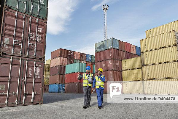 Arbeiter und Geschäftsmann im Gespräch in der Nähe von Frachtcontainern