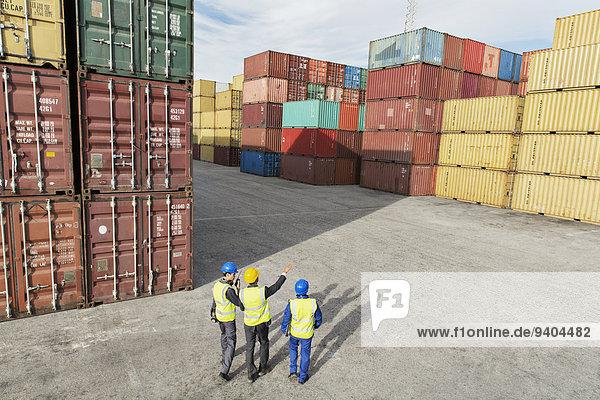 Geschäftsleute und Arbeiter im Gespräch in der Nähe von Frachtcontainern