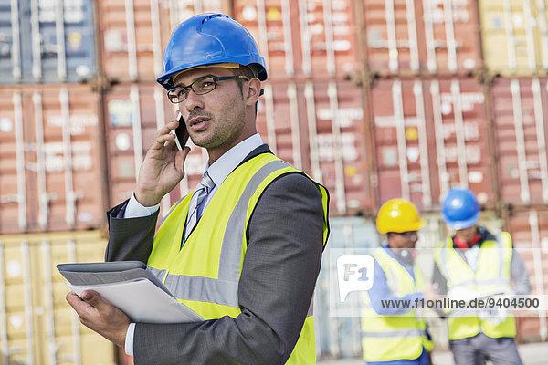 Geschäftsmann im Gespräch am Handy in der Nähe von Frachtcontainern