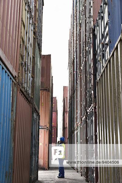 Arbeiter steht zwischen Frachtcontainern