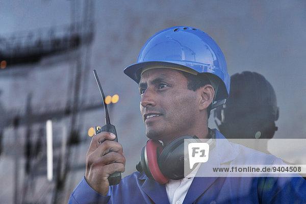 Arbeiter hält Walkie-Talkie in der Nähe des Fensters